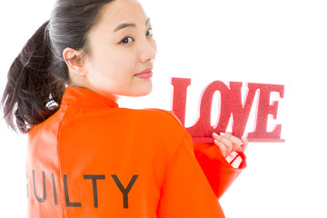 "Asian young woman holding a red ""LOVE"" text in prisoners uniform"
