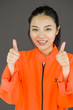 Young Asian woman showing thumb up sign with both hands in