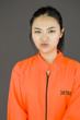 Upset young Asian woman in prisoners uniform