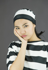 Upset young Asian woman in prisoners uniform with her hands on