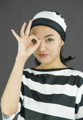 Young Asian woman showing OK sign in prisoners uniform