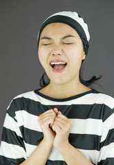 Asian young woman pleading in prisoners uniform
