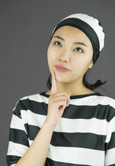 Young Asian woman with finger on chin in prisoners uniform