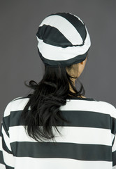 Rear view of a young Asian woman in prisoners uniform
