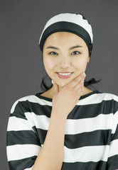 Young Asian woman with hand on chin in prisoners uniform