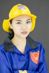 Close up of a lady firefighter wearing yellow helmet and blue