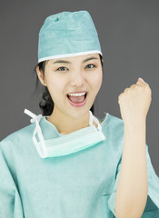 Asian female surgeon punches fist into the air isolated on