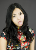 Asian young woman poking out tongue towards camera isolated on poster