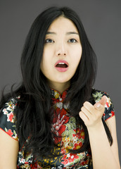 Shocked Asian young woman with pointing isolated on colored