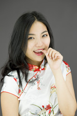 Asian young woman smiling with finger in mouth