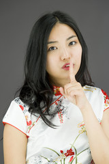 Asian young woman with finger on lips