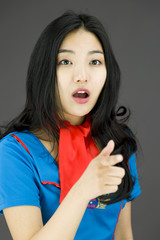 Shocked Asian air stewardess with pointing isolated on colored
