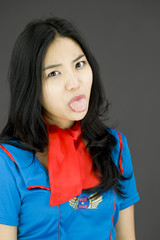 Asian air stewardess poking out tongue towards camera