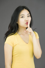 Young Asian woman with finger on lips