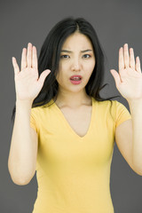 Young Asian woman making stop gesture sign from both hands