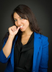 Young businesswoman with finger in mouth and smiling
