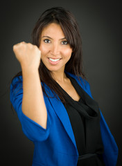 Portrait of a young businesswoman showing fist and celebrating