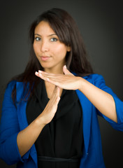 Young businesswoman making time out signal with hands