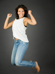 Excited and cheerful young woman jumping in air and smiling