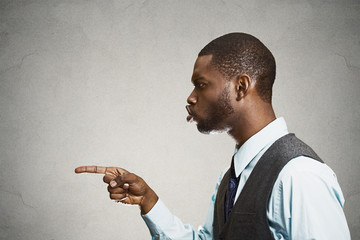Side view portrait man pointing at someone accusing wrong doing