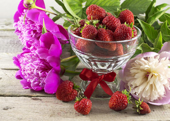 Strawberryies in glass bowl with peony flowers