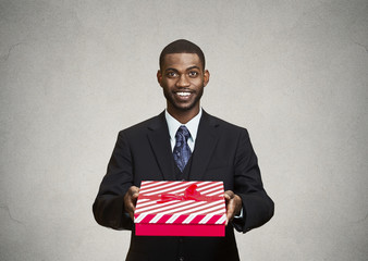 Happy businessman giving gift box to someone
