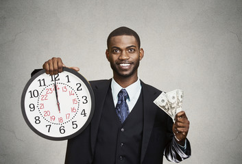 Businessman holding wall clock and cash in hands. Time is money