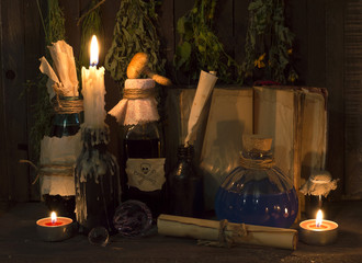 Homeopathic still life with book and bottles in candle light