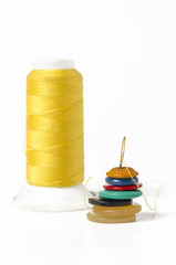 Yellow thread with needle and buttons
