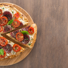 Italian pizza with salami and tomatoes on wooden background