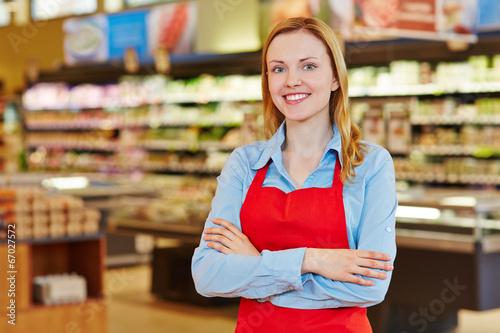 Leinwanddruck Bild Junge Verkäuferin im Supermarkt