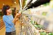 Leinwanddruck Bild - Frau kauft Joghurt im Supermarkt