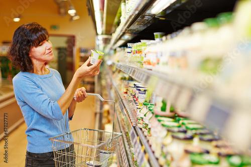 Leinwanddruck Bild Frau kauft Joghurt im Supermarkt