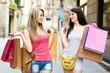 Two smiling young women doing shopping