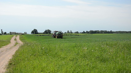 tractor with sprayers rides through crop field