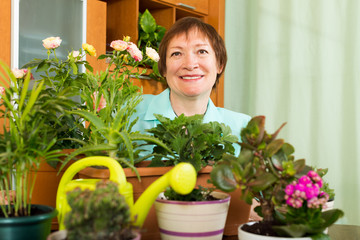 Female mature gardener with plants smiling