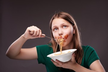 Teen girl eating pasta