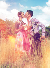 Loving Bavarian couple kiss each other in nature
