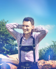 Handsome guy wears a Lederhosen and poses outside