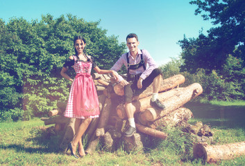 Couple in Bavarian clothes posing in countryside