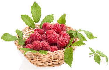 Raspberries in woven basket with green leaves
