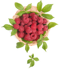 View from above of raspberries in a basket with leaves