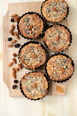 Small tarts with nuts and raisins filling on a wooden board.