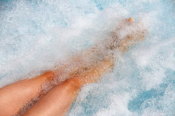 beautiful women legs in the bathtub with Whirlpool with water to