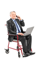 Mature businessman working on laptop in a wheelchair
