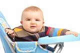 Joyful baby boy sitting in a feeding chair
