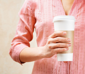 Young woman holding a tumbler of coffee