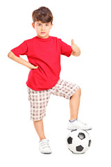 Kid with a football under his foot giving a thumb up