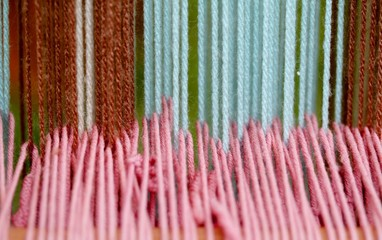strong woolen threads woven into the loom