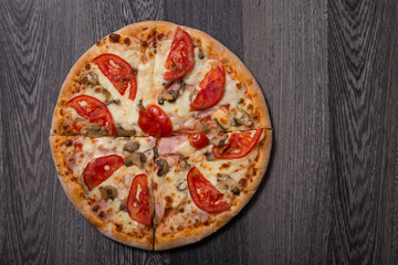 High angle view of delicious Italian pizza with ham and tomatoes